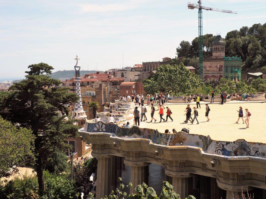 Die von Säulen getragene Terrasse, gesäumt von einer Bank mit Bruchkeramik verziert im Parc Güell in Barcelona
